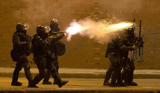 A military police fires tear gas at protestors during an anti-government demonstration in Rio de Janeiro, Brazil, Thursday, June 20, 2013. (AP Photo/Victor R. Caivano)