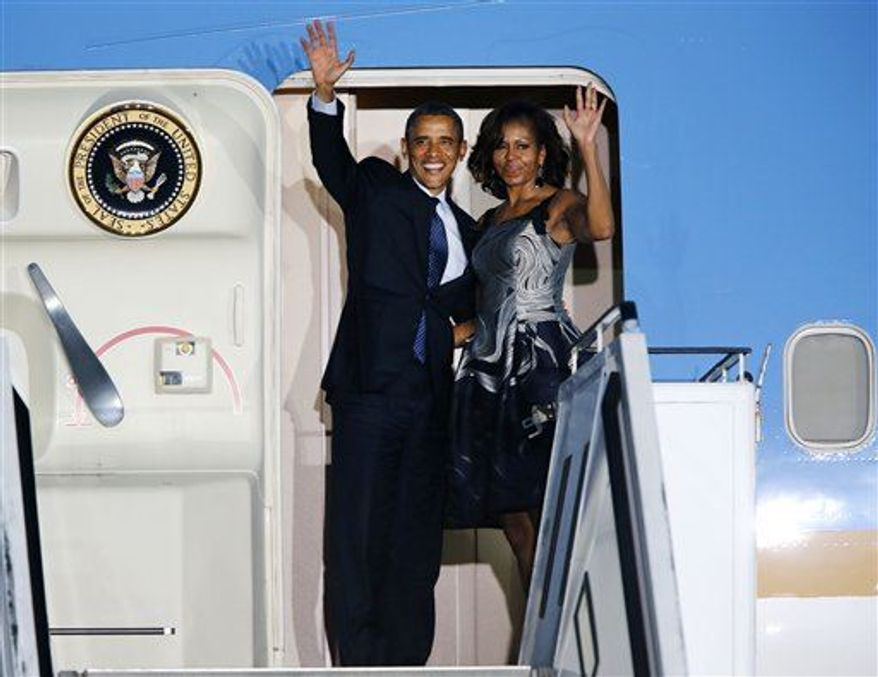 President Obama and first lady Michelle Obama wave goodbye from Air Force One at the Tegel airport in Berlin Wednesday, June 19, 2013. Obama was for a two-day official visit to Germany. (Associated Press)