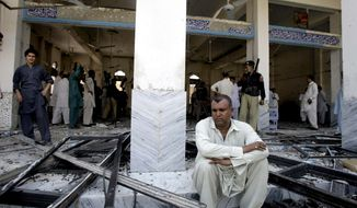 A man sits at a Shiite mosque targeted by a suicide bomber in Peshawar, Pakistan, on Friday, June 21, 2013. Militants opened fire on a Shiite Muslim mosque where worshippers were gathering for Friday prayers, and then a suicide bomber detonated his explosives inside, killing more than a dozen people in the latest attack aimed at the minority sect, police said. (AP Photo/Mohammad Sajjad)