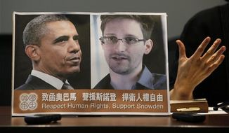 Pro-democractic legislator Claudia Mo Man-ching speaks next to a picture of President Obama and Edward Snowden during a news conference in Hong Kong Friday, June 14, 2013. (Associated Press)