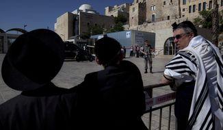 A border police officer stands guard as ultra-Orthodox Jewish men look at the scene of a shooting at the plaza of the Western Wall, the holiest site where Jews can pray, in Jerusalem's old city, Friday, June 21, 2013. Israeli police say a guard has shot a Jewish man dead at the key Jerusalem holy site. (AP Photo/Sebastian Scheiner)