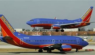 ** FILE ** A Southwest Airlines Boeing 737 waits to take off at Chicago's Midway International Airport as another lands on Feb. 10, 2012. (Associated Press)