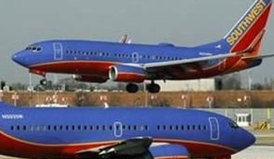 ** FILE ** A Southwest Airlines Boeing 737 waits to take off at Chicago's Midway Airport as another land, Feb. 10, 21012. (Associated Press)