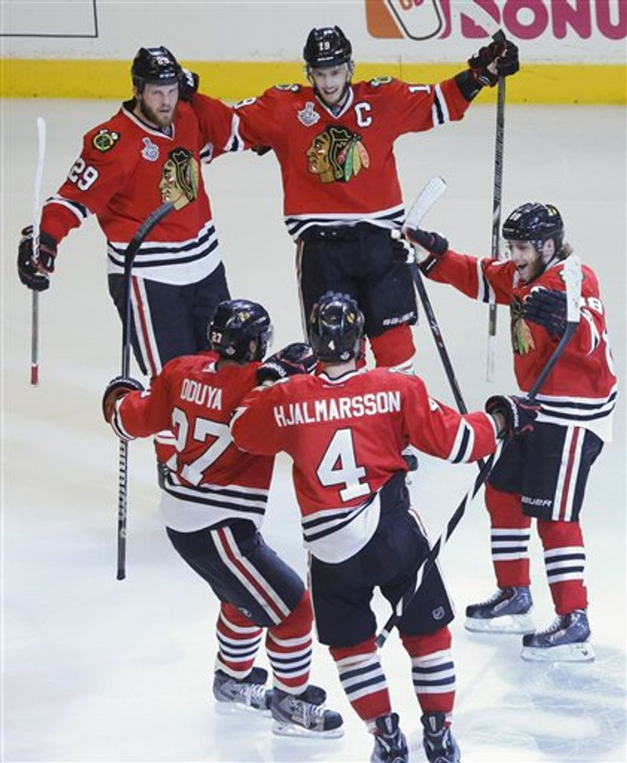 The Chicago Blackhawks celebrate a first period goal against the Boston Bruins during Game 5 of the NHL hockey Stanley Cup Finals, Saturday, June 22, 2013, in Chicago. (AP Photo/Nam Y. Huh)