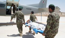 Under the careful watch of coalition advisers, members of the Kandahar Air Wing carry an injured Afghan soldier onto a Cessna 208. The Afghan air force is far from ready to take over combat responsibilities from NATO. (Kristina Wong/The Washington Times)