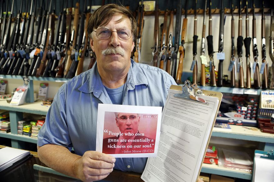 **FILE** Paradise Firearms owner Paul Paradis holds a flyer depicting Colorado's State Senate President, Democrat John Morse, together with a petition to recall him at his gun shop in Colorado Springs, Colo., on May 24, 2013. Paradis and other gun-rights activists are seeking the ouster of Morse for his support of new laws that restrict ammunition magazines and expand background checks to include private gun sales. (Associated Press)