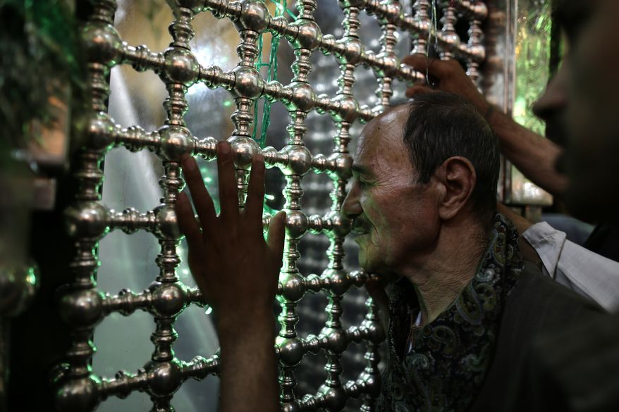 Egyptians pray at the shrine of Sayyeda Zeinab, sister of Imam Hussein, who was the grandson of Islam's Prophet Muhammad and one of the most believed Shiite saints, in Cairo on Tuesday, June 4, 2013. Hatreds between Shiites and Sunnis are now more virulent than ever in the Arab world because of Syria's brutal civil war. Hard-line clerics and politicians on both sides have added fuel, depicting the fight as essentially a war of survival for their sect. (AP Photo/Hassan Ammar)