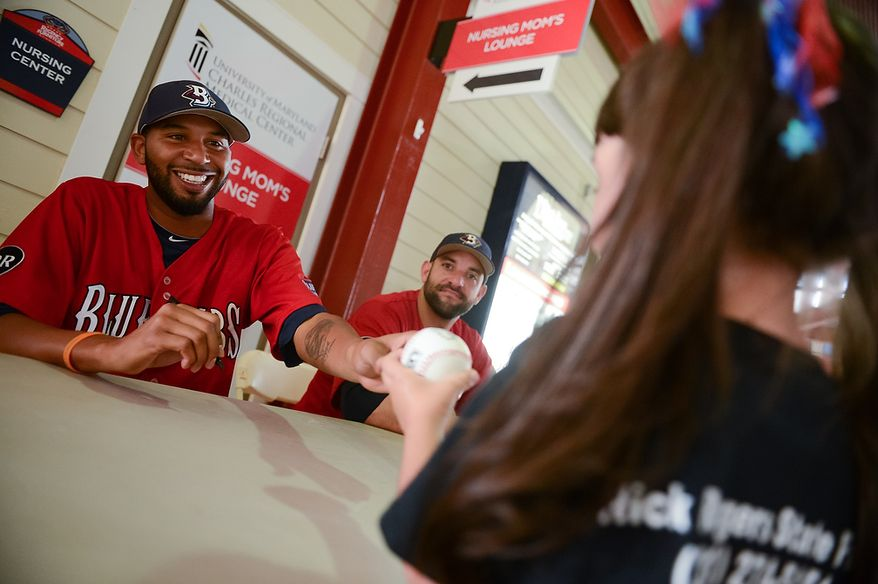 Laura Coldin, 5, of Mechanicsville, Va., right, gets her baseball autographed by Blue Crabs pitcher Daryl Thompson (3) at Regency Furniture Stadium, Waldorf, Md., Sunday, June 23, 2013. The Blue Crabs played the Camden RiverSharks, both teams part of the independent baseball leagues. (Andrew Harnik/The Washington Times)