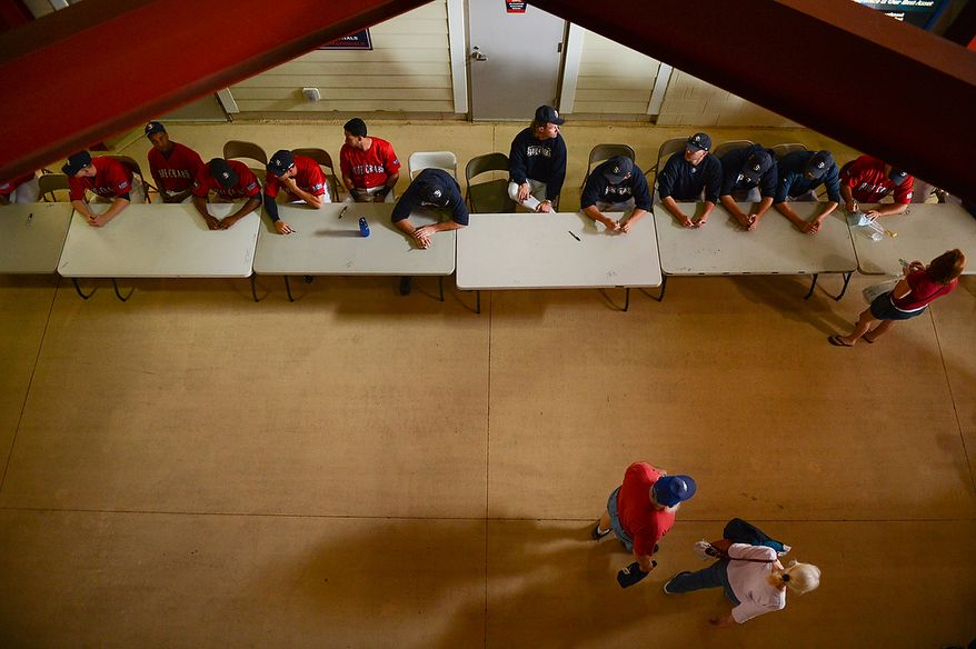 Players for the Blue Crabs sit and sign autographs before the independent baseball league's Blue Crabs play the Camden RiverSharks at Regency Furniture Stadium, Waldorf, Md., Sunday, June 23, 2013. (Andrew Harnik/The Washington Times)