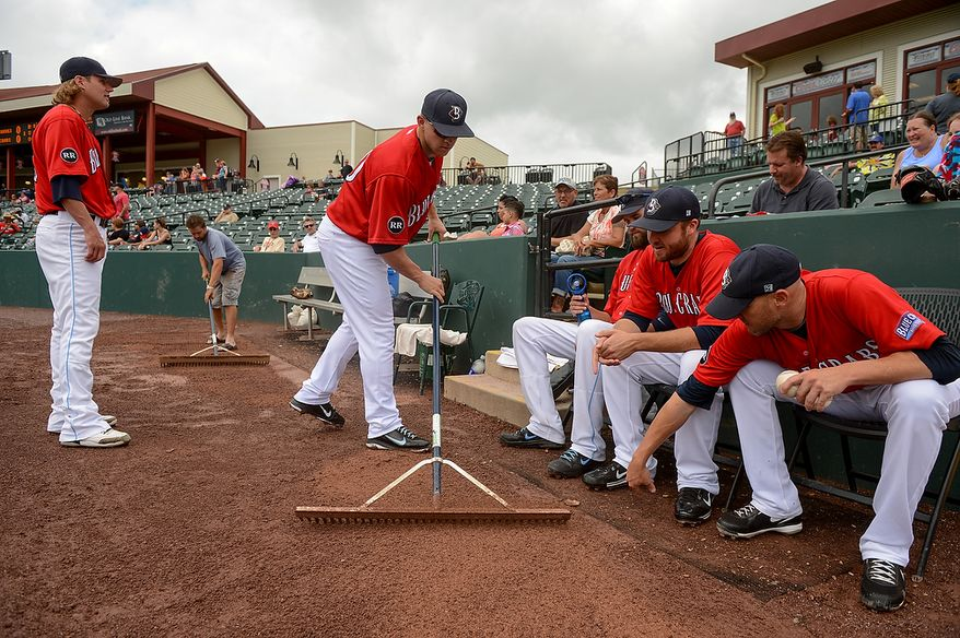 Pitcher Kyle Mertins (40), center, helps the ground crew sweep the dirt around the bullpen before the independent baseball league's Blue Crabs play the Camden RiverSharks at Regency Furniture Stadium, Waldorf, Md., Sunday, June 23, 2013. (Andrew Harnik/The Washington Times)