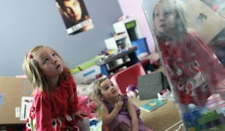 ** FILE ** With her face reflected in a mirror, Coy Mathis, left, a transgender girl, plays with her sister, Auri, 2, center, at their home in Fountain, Colo., on Monday, Feb. 25, 2013. (AP Photo/Brennan Linsley)
