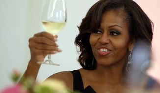 **FILE** First lady Michelle Obama raises her glass for a toast during a dinner at the Charlottenburg palace in Berlin on June 19, 2013. (Associated Press)
