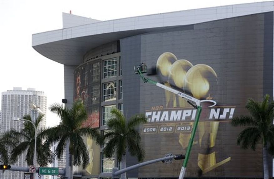 Workers on a boom prepare the outside of the American Airlines Arena before a parade and celebration for the NBA Champion Miami Heat basketball team, Monday, June 24, 2013 in Miami. (AP Photo/Wilfredo Lee)