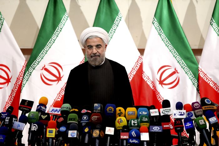 ** FILE ** Iranian newly elected President Hasan Rouhani, listens to the Iranian national anthem, before beginning a press conference, in Tehran, Iran, June 17, 2013. (AP Photo/Ebrahim Noroozi)
