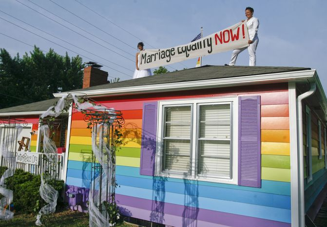 Kimberly Kidwell (right) and her partner, Katie Short, hold up a marriage equality sign on top of the Equality House before their wedding on Saturday, June 22, 2013, in Topeka, Kan. (AP Photo/The Topeka Capital Journal, Chris Neal)