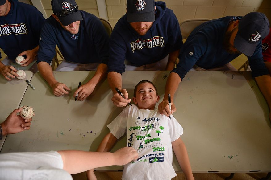 Jeremiah Collins, 10, of Lexintgon Park, Md., lays down on a table to get his t-shirt autographed by Blue Crabs pitchers Michael Ballard (48) center, and Jim Ed Warden (34), right, at Regency Furniture Stadium, Waldorf, Md., Sunday, June 23, 2013. Also pictured is pitcher Charlie Manning (6), second from left. The Blue Crabs played the Camden RiverSharks, both teams part of the independent baseball leagues. (Andrew Harnik/The Washington Times)