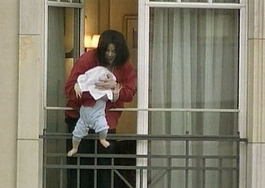 **FILE** Michael Jackson holds his child Prince Michael II, his head hidden by a towel, over a balcony of the Adlon Hotel in Berlin on Nov. 19, 2002, in this photo made from video. Jackson, in Germany to attend an awards ceremony, had been waving to German fans, when he brought the baby onto the balcony. (Associated Press/APTN)