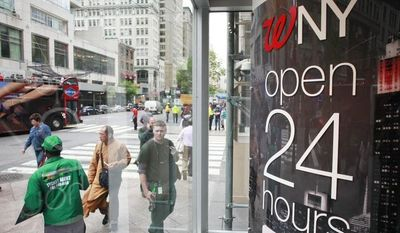 Pedestrians enter and leave the Walgreen flagship store in the Empire State Building in New York on Wednesday, May 15, 2013. (AP Photo/Mark Lennihan)