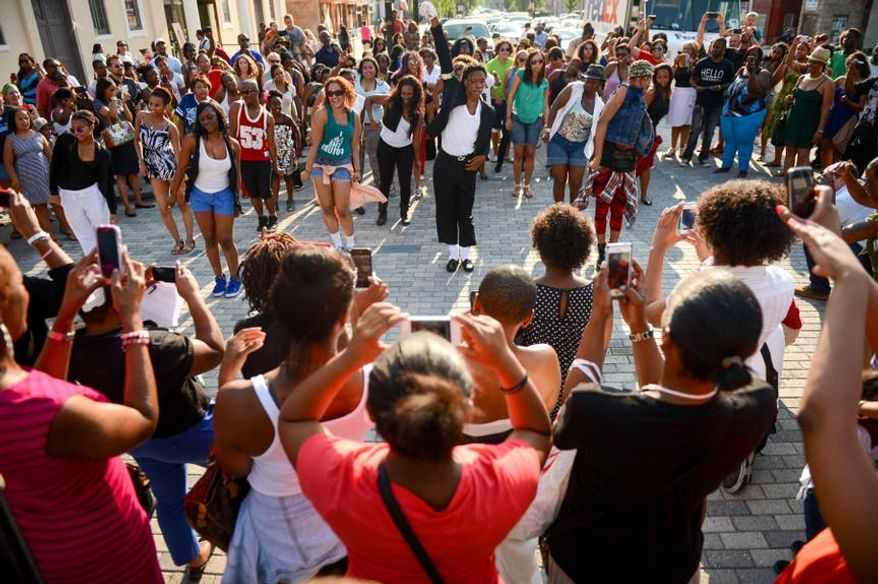 "Hill, Md., dresses as Michael Jackson, center, leads a group of dancers to Michael Jackson's ""Beat It"" during a flash mob in front of the Howard Theatre to celebrate the life of the King of Pop on the 4th anniversary of his death, Washington, D.C., Tuesday, June 25, 2013. (Andrew Harnik/The Washington Times)"