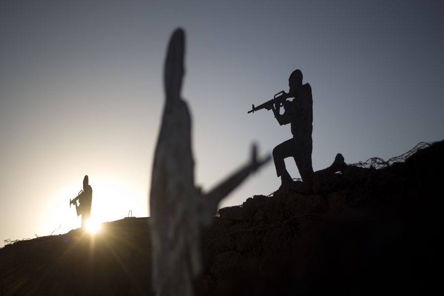 Metal placards in the shape of Israeli soldiers sit on an old bunker at an observation point on Mt. Bental in the Israeli controlled Golan Heights, overlooking the border with Syria, on June 24, 2013. (Associated Press)