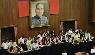 Lawmakers occupy the legislature floor, preventing the session from continuing, as Chinese activist Chen Guangcheng speaks to lawmakers and human rights supporters at a nearby auditorium at the legislature compound in Taipei, Taiwan, on Tuesday, June 25, 2013. (AP Photo/Wally Santana)