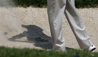 **FILE** Tiger Woods casts a shadow as he hits out of a bunker on the second hole during the third round of the AT&T National golf tournament at Congressional Country Club in Bethesda, Md., Saturday, June 30, 2012. (AP Photo/Patrick Semansky)