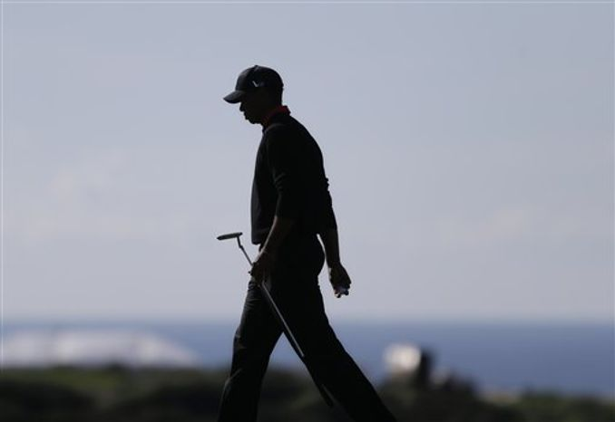 **FILE** Tiger Woods is silhouetted as he walks across the 14th green during the final round in the Farmers Insurance Open golf tournament Monday, Jan. 28, 2013, in San Diego. (AP Photo/Lenny Ignelzi)