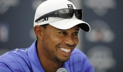 Tiger Woods reacts at a press conference at the AT&T National Golf tournament, Wednesday, July 26, 2013, in Bethesda, Md. Woods will not play in the tournament because of a left elbow strain. (AP Photo/Nick Wass)