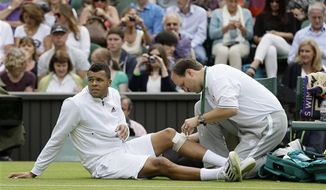 Jo-Wilfried Tsonga of France is treated during his Men's second round singles match against Ernests Gulbis of Latvia at the All England Lawn Tennis Championships in Wimbledon, London, Wednesday, June 26, 2013. (AP Photo/Alastair Grant)