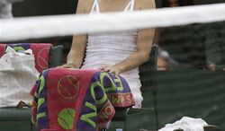 Maria Sharapova of Russia waits for play to resume during her Women's second round singles match against Michelle Larcher De Brito of Portugal at the All England Lawn Tennis Championships in Wimbledon, London, Wednesday, June 26, 2013. (AP Photo/Anja Niedringhaus)