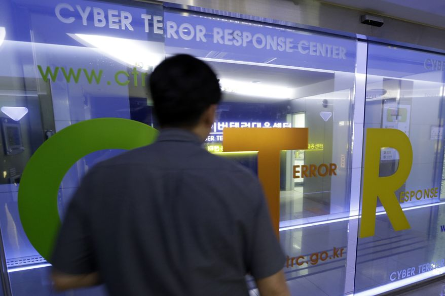 A man walks by a gate at Cyber Terror Response Center of National Police Agency in Seoul on Tuesday, June 25, 2013. South Korea said multiple government and private sector websites were hacked on Tuesday's anniversary of the start of the Korean War, and Seoul issued a cyberattack alert warning officials and citizens to take security measures. (Associated Press)