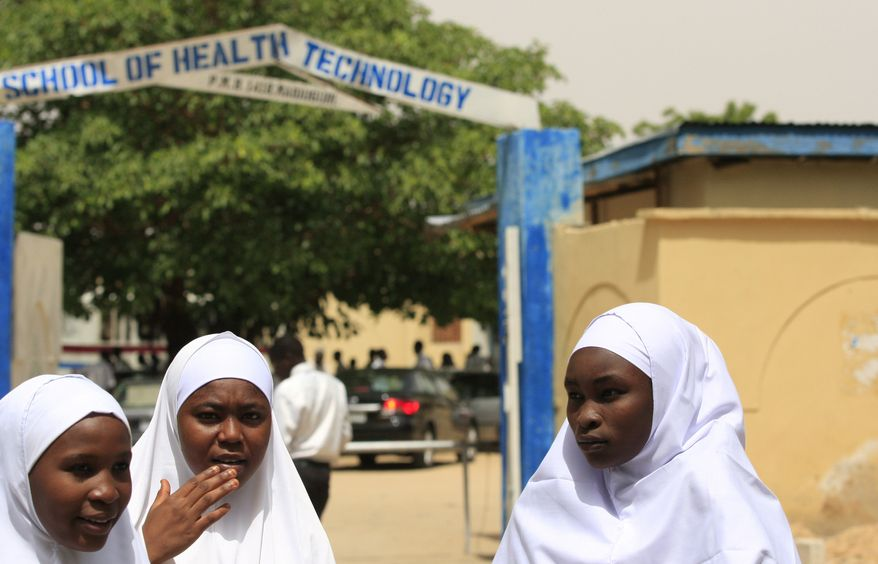 ** FILE ** Young women stand in front of a school in Maiduguri, Nigeria, on Thursday, June 6, 2013. Boko Haram, the radical group that once attacked only government institutions and security forces, increasingly is targeting civilians. (AP Photo/Jon Gambrell)