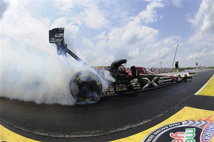 ** FILE ** Spencer Massey performs a burnout in his Schumacher Electric dragster en route to winning the NHRA New England Nationals auto race at New England Dragway, Sunday, June 23, 2013, in Epping, N.H. (Associated Press)