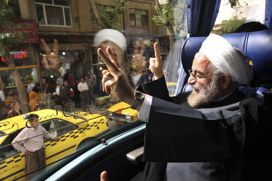 In this Monday, June 10, 2013, photo, Iranian President-elect, Hasan Rouhani, a former Iran's top nuclear negotiator, waves, from his bus, during his presidential election campaign tour to the western city of Sanandaj, Iran. (AP Photo/Vahid Salemi)