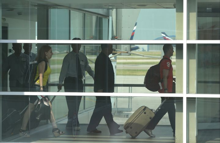 ** FILE ** Passengers walk to board Aeroflot flight SU150 from Moscow to Havana, at Sheremetyevo airport in Moscow on June 27, 2013. (Associated Press)