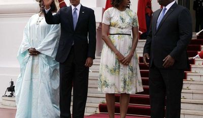 U.S. President Barack Obama waves as he poses for a picture alongside U.S. First Lady Michelle Obama, second right, Senegalese President Macky Sall, right, and Senegalese First Lady Mariame Faye Sall at the presidential palace in Dakar, Senegal, Thursday, June 27, 2013. (AP Photo/Rebecca Blackwell)