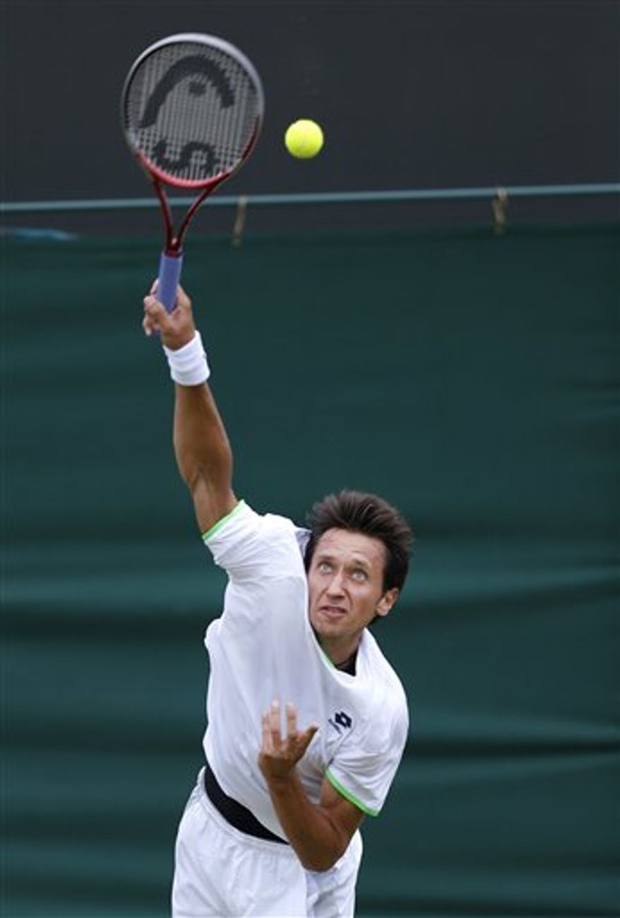 Sergiy Stakhovsky of Ukraine serves to Jurgen Melzer of Austria during their Men's second round singles match at the All England Lawn Tennis Championships in Wimbledon, London, Friday, June 28, 2013. (AP Photo/Sang Tan)