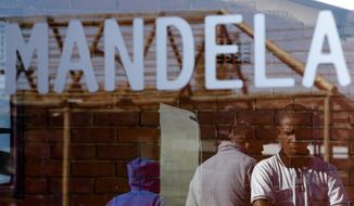 People are reflected in a window of the house of former South African President Nelson Mandela in Soweto on June 28, 2013. Members of Mandela's family as well as South African Cabinet ministers have visited the hospital where the 94-year-old former president is critically ill. (Associated Press)