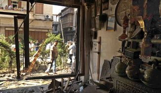 This photo released by the Syrian official news agency SANA, shows a Syrian security agent looking at a damaged antique shop after a blast struck in the vicinity of the Greek Orthodox Virgin Mary Church in the predominantly Christian neighborhood of Bab Sharqi in central Damascus, Syria, Thursday, June 27, 2013. (AP Photo/SANA)
