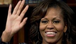 U.S. first lady Michelle Obama waves to the audience during a youth event at the Sci-Bono Discovery Centre, Saturday, June 29, 2013, in Johannesburg, South Africa, organized in conjunction with MTV Base, an African youth and music TV channel, and Google+ to highlight the importance of education. (AP Photo/Carolyn Kaster)
