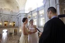 Elizabeth Carey (left) and Cynthia Wides exchange wedding vows at City Hall in San Francisco on Saturday, June 29, 2013. (AP Photo/Marcio Jose Sanchez)