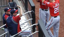 Washington Nationals' Adam LaRoche (25) is greeted by Ian Desmond (20) and teammates after hitting a solo home run off of New York Mets starting pitcher Zack Wheeler in the second inning of a baseball game at Citi Field on Sunday, June 30, 2013 in New York. (AP Photo/Kathy Kmonicek)