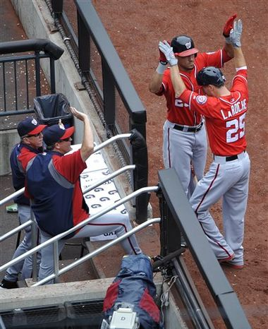 Washington Nationals' Adam LaRoche (25) is greeted by Ian Desmond (20) and teammates after hitting a solo home run off of New York Mets starting pitcher Zack Wheeler in the second inni