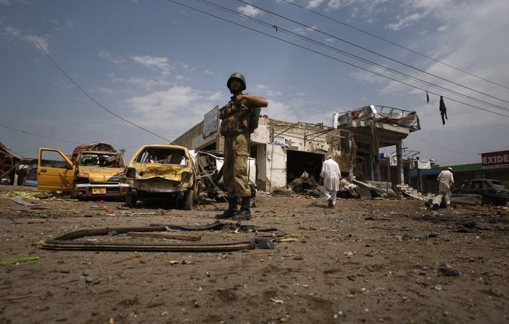 A Pakistani soldier examines the site of a car bombing on the outskirts of Peshawar, Pakistan, on Sunday, June 30, 2013. The blast occurred as a convoy of paramilitary troops passed through the outskirts of the northwest Pakistani city, police said. (AP Photo/Mohammad Sajjad)