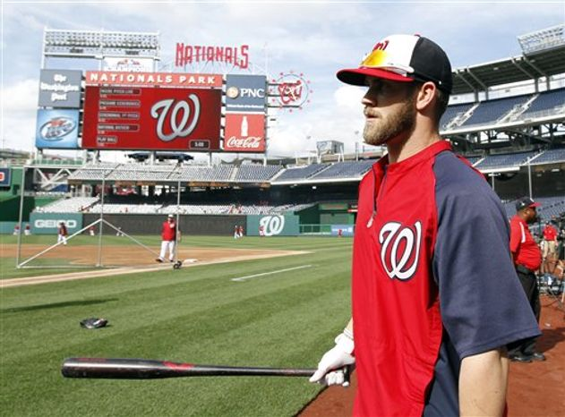 Washington Nationals left fielder Bryce Harper carries his bat to batting practice before a baseball game against the Milwaukee Brewers at Nationals Park Monday, July 1, 201