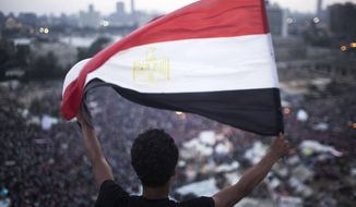 "An Egyptian protester waves a flag in Tahrir Square during a demonstration against Egypt's Islamist President Mohammed Morsi in Cairo on July 1, 2013. Egypt's powerful military warned it will intervene if the Islamist president doesn't ""meet the people's demands,"" giving him and his opponents two days to reach an agreement in what it called a last chance. Hundreds of thousands of protesters massed for a second day calling on Morsi to step down. (Associated Press)"