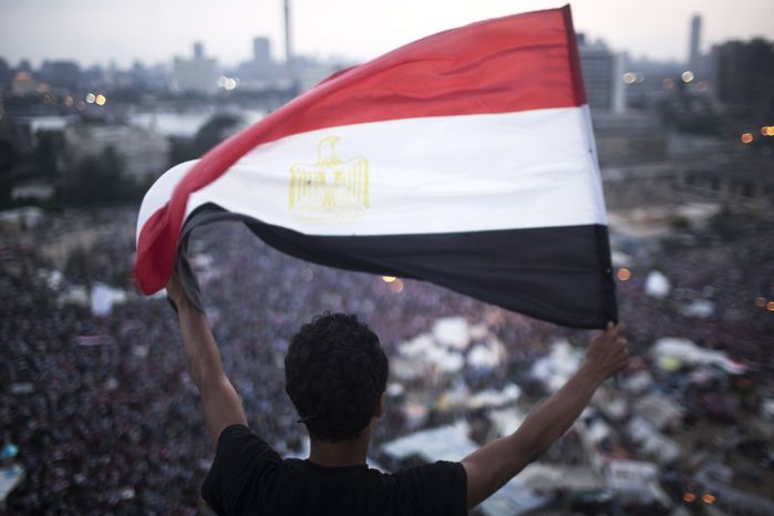 """An Egyptian protester waves a flag in Tahrir Square during a demonstration against Egypt's Islamist President Mohammed Morsi in Cairo on July 1, 2013. Egypt's powerful military warned it will intervene if the Islamist president doesn't """"meet the people's demands,"""" giving him and his opponents two days to reach an agreement in what it called a last chance. Hundreds of thousands of protesters massed for a second day calling on Morsi to step down. (Associated Press)"""