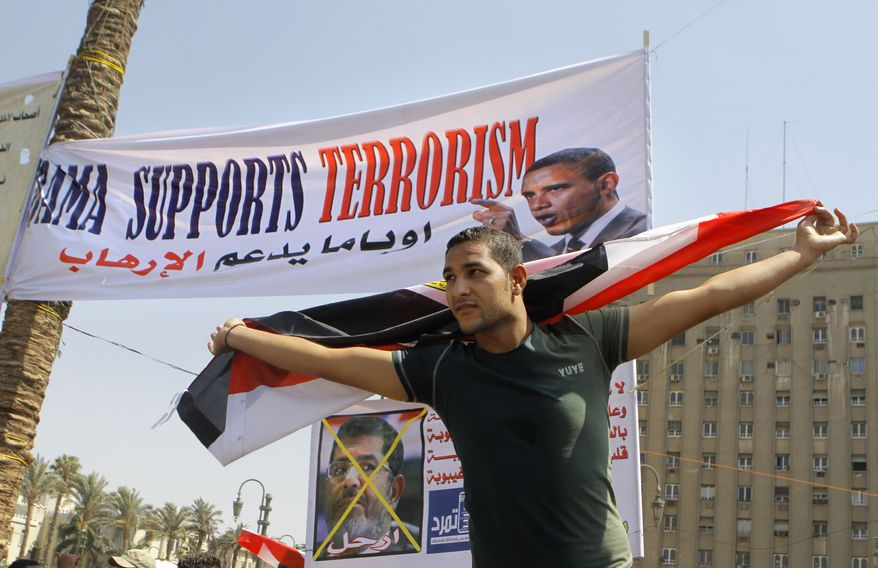 """An Egyptian protesting President Mohammed Morsi waves a national flag in front of a banner criticizing Morsi and U.S. President Barack Obama in Tahrir Square, the focal point of Egyptian uprising, in Cairo on June 30, 2013. Thousands of opponents and supporters of the president began massing in city squares in competing rallies, gearing up for a day of massive nationwide protests that many fear could turn deadly as the opposition seeks to push out Mohammed Morsi. Arabic reads, """"Leave."""" (Associated Press)"""