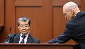 Don West (right), George Zimmerman's defense attorney, presents state witness Hirotaka Nakasone (left), a senior voice recognition scientist with the FBI, with a marked exhibit as Mr. Nakasone testifies in Mr. Zimmerman's trial in Seminole Circuit Court in Sanford, Fla., on Monday, July 1, 2013. Mr. Zimmerman is charged with second-degree murder in the 2012 shooting death of Trayvon Martin. (AP Photo/Orlando Sentinel, Joe Burbank, Pool)