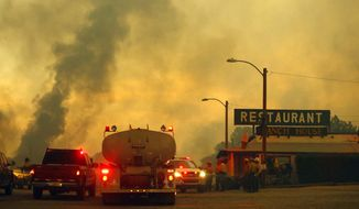 Firefighters monitor a restaurant as the Yarnell Hill Fire burns on Sunday, June 30, 2013, near Yarnell, Ariz. The fire started Friday and picked up momentum as the area experienced high temperatures, low humidity and windy conditions. It has forced the evacuation of residents in the Peeples Valley area and in the town of Yarnell. (AP Photo/The Arizona Republic, David Kadlubowski)